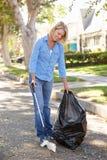 拾起在郊区街道的妇女废弃物 库存照片