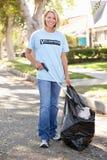 拾起在郊区街道的妇女废弃物 库存图片