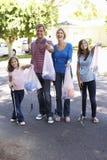 拾起在郊区街道的家庭废弃物 库存照片
