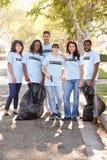 拾起在郊区街道的志愿者队废弃物 库存照片