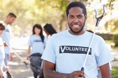 拾起在郊区街道的志愿者队废弃物 库存图片