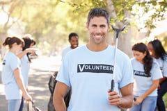 拾起在郊区街道的志愿者队废弃物 免版税图库摄影