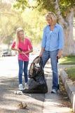 拾起在郊区街道的母亲和女儿废弃物 免版税库存图片