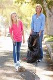 拾起在郊区街道的母亲和女儿废弃物 库存图片