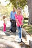 拾起在郊区街道的母亲和女儿废弃物 库存照片