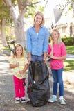 拾起在郊区街道的母亲和女儿废弃物 免版税库存照片