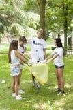 拾起废弃物的小组年轻志愿者在公园 免版税库存照片
