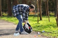 拾起废弃物的年轻人志愿者 库存图片