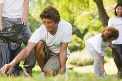 拾起废弃物的志愿者队在公园 库存图片