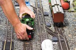 拾起火车模型集合的手 库存图片