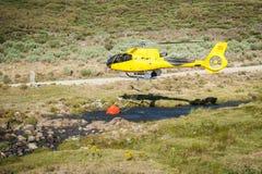 拾起从小河的直升机消防队员水 免版税库存照片