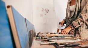 拾起从桌的女性艺术家工具 库存图片