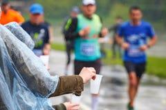 拾起水的未认出的马拉松运动员在服务点在16 Cracovia马拉松期间 免版税库存图片