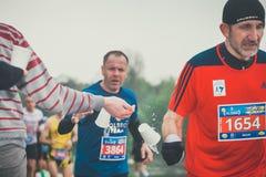 拾起水的未认出的马拉松运动员在服务点在16 Cracovia马拉松期间 免版税库存照片