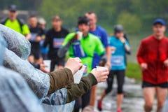 拾起水的未认出的马拉松运动员在服务点在16 Cracovia马拉松期间 图库摄影