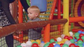 拿到从干燥水池的球的小的白肤金发的男孩尝试与球hismother在干燥水池投入他 影视素材