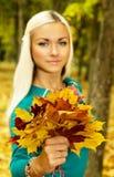 拿着一一抱叶子的秋天天气的美丽的金发碧眼的女人 免版税库存图片