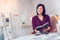 拿着一个个人组织者的快乐的精力充沛的微笑的引诱的短发夫人 图库摄影