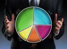 拿着一个五颜六色的圆形统计图表的商人 免版税库存照片