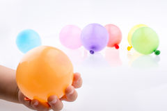 拿着一个五颜六色的小气球的手手中 免版税库存照片