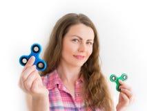 拿着一个五颜六色的手坐立不安锭床工人玩具的女孩 免版税库存图片