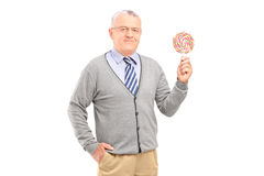 拿着一个五颜六色的棒棒糖的资深绅士 免版税图库摄影