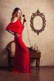 拿着一个减速火箭的电话的红色礼服的女孩 库存照片