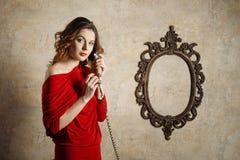 拿着一个减速火箭的电话的红色礼服的女孩 免版税库存照片