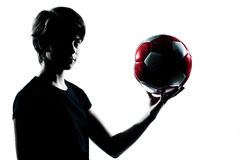 拿着一个剪影足球少年的footba 免版税库存图片