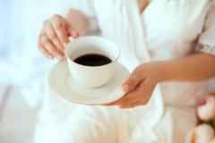 拿着一个加奶咖啡杯子的女孩 在一件白色外套 免版税库存照片