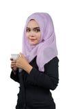 拿着一个加奶咖啡杯子的美丽的现代年轻亚裔回教女商人 免版税图库摄影