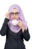 拿着一个加奶咖啡杯子的美丽的现代年轻亚裔回教女商人 免版税库存图片