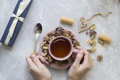拿着一个午后茶会杯子和匙子, giftbox,曲奇饼的手 免版税库存照片
