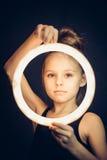 拿着一个发光的圈子的美丽的女孩体操运动员 免版税图库摄影