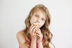 拿着一个可口开胃蛋糕的小女孩 库存图片