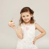 拿着一个可口蛋糕用樱桃的小女孩 免版税库存照片