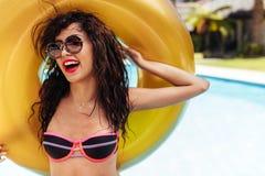 拿着一个可膨胀的圆环的比基尼泳装的美丽的妇女在游泳池边 库存图片