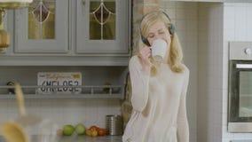拿着一个咖啡杯的愉快的妇女在听到在她的耳机的音乐的厨房里 影视素材