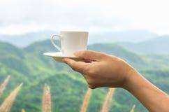拿着一个咖啡杯 免版税图库摄影