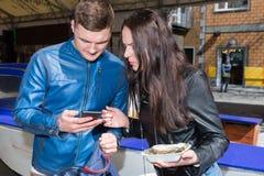 拿着一个唯一新鲜的被打开的牡蛎和电话的年轻夫妇 库存照片