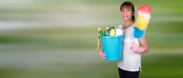 拿着一个喷粉器和一个桶用清洁设备的主妇 免版税图库摄影