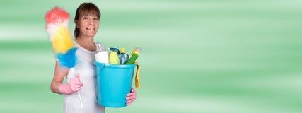 拿着一个喷粉器和一个桶用清洁设备的主妇 免版税库存图片