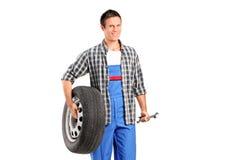 拿着一个备用轮胎和板钳的技工 库存图片