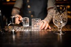 拿着一个大冰块的侍酒者在空的玻璃附近 库存图片