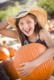 拿着一个大南瓜的笑的女牛仔在南瓜补丁 免版税库存照片