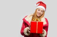 拿着一个大圣诞节礼物的美丽的红色头发妇女 免版税图库摄影