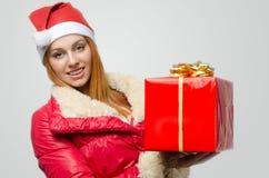 拿着一个大圣诞节礼物的美丽的红色头发妇女 库存图片