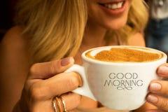 拿着一个大杯子热奶咖啡的咖啡馆的微笑的少女与咖啡泡沫设计和词早晨好在杯子 图库摄影