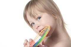 拿着一个大棒棒糖的美丽的小女孩 免版税库存图片