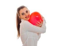 拿着一个大气球的年轻微笑的女孩以心脏的形式 图库摄影
